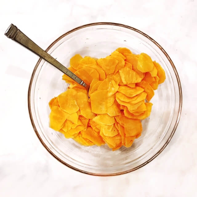 A glass bowl filled with freshly sliced sweet potatoes with a silver spoon protruding out on a white marbled surface