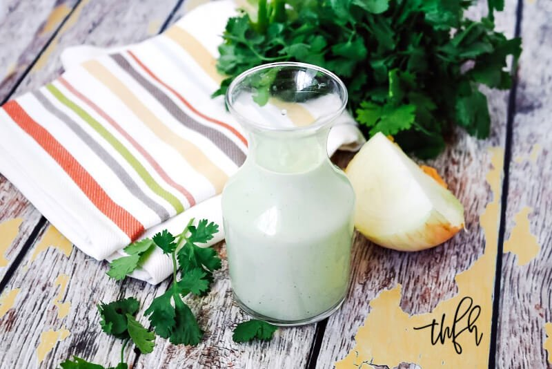 A small glass container filled with Gluten-Free Vegan Creamy Jalapeno Dressing next to a bundle of fresh cilantro and a striped cloth napkin
