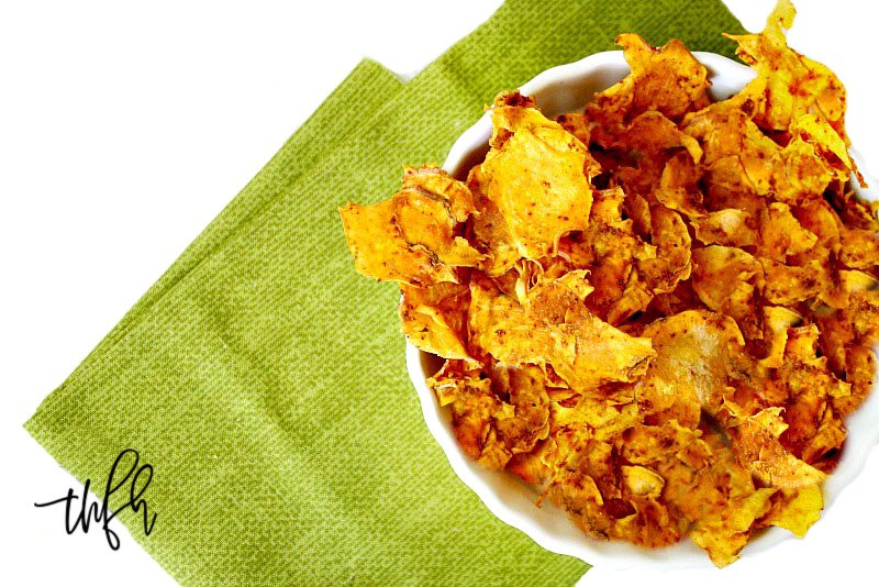 Overhead horizontal image of a white bowl filled with sweet potato chips on top of a green napkin on a solid white background