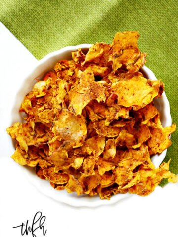 A vertical overhead image of a white bowl filled with Gluten-Free Vegan Dehydrated Sweet Potato Chips on a green napkin on top of a solid white background