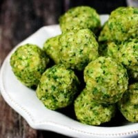 White bowl full of Gluten-Free Vegan Raw No-Cook Broccoli Balls on a wooden surface