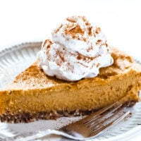 Horizontal image of a slice of Gluten-Free Vegan No-Bake Pumpkin Pie on a decorative grey plate next to a silver fork with a large dollop of vegan whipped cream on top