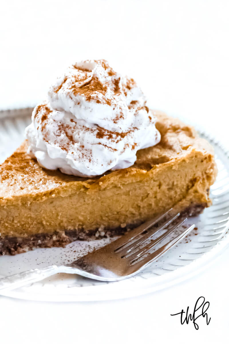 Close-up vertical image of a slice of Gluten-Free Vegan No-Bake Pumpkin Pie with a large dollop of vegan whipped cream on a grey plate next to a silver fork on a solid white background