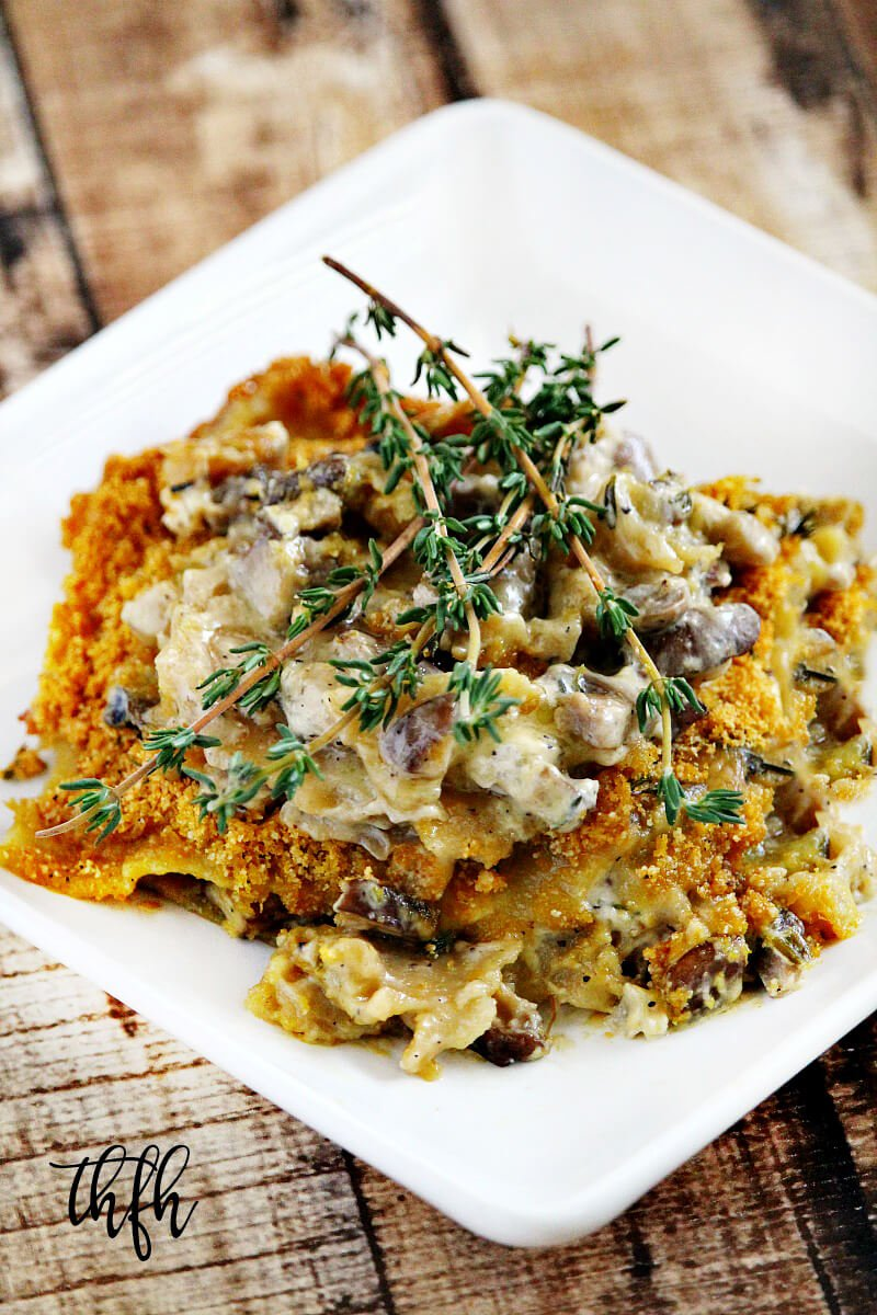 Vertical image of Gluten-Free Vegan Creamy Mushroom Lasagna on a white plate on a wooden surface