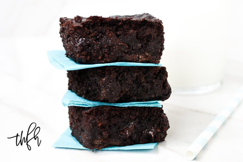 Close up image of a stack of three of The BEST Gluten-Free Vegan Flourless Zucchini Brownies between aqua napkins on a white surface