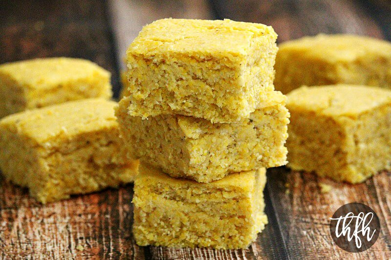 Stack of three sliced squares of The BEST Homemade Vegan Cornbread on a weathered wooden surface with more cornbread slices in the background