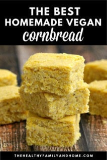 A close-up image of a stack of three squares of The BEST Homemade Vegan Cornbread on a weathered wooden surface with text overlay