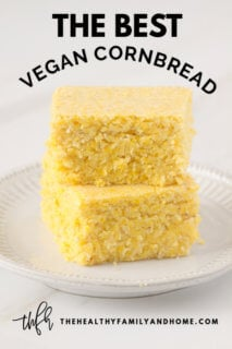 Stack of 2 of The BEST Vegan Cornbread Squares on a white plate on a white marble surface with Pinterest text overlay