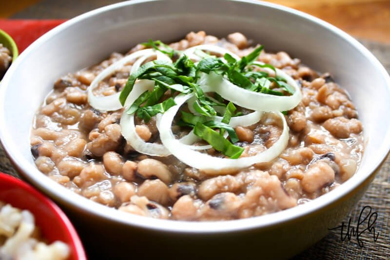 Close-up image of a bowl filled with Gluten-Free Vegan Instant Pot Black-Eyed Peas garnished with sliced white onions and chopped greens