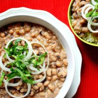 Horizontal overhead view of two bowls of Easy Vegan Slow Cooker Black Eyed Peas in a white bowl on a red background