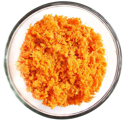 Overhead image of a glass bowl of carrot pulp to make Gluten-Free Vegan Raw Carrot Pulp and Flax Seed Crackers