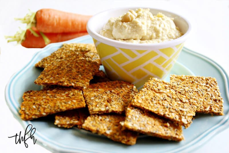 Horizontal image of a blue plate filled with Gluten-Free Vegan Raw Carrot Pulp and Flax Seed Crackers next to a bowl of hummus on a white background