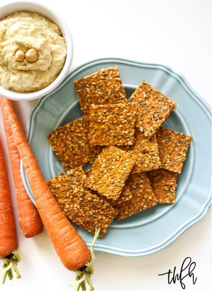 Vertical image of a blue plate full of Gluten-Free Vegan Raw Carrot Pulp and Flax Seed Crackers on a white background