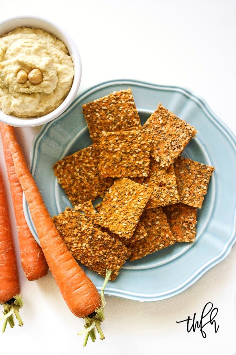 Overhead image of a blue plate filled with Gluten-Free Vegan Raw Carrot Pulp and Flax Seed Crackers next to a bowl of hummus on a white background