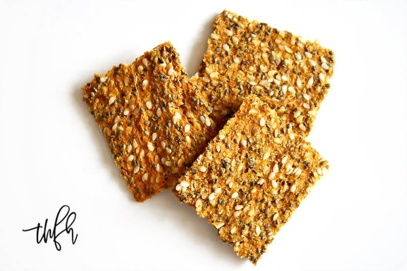 Overhead image of three Gluten-Free Vegan Raw Carrot Pulp and Flax Seed Crackers on a white background