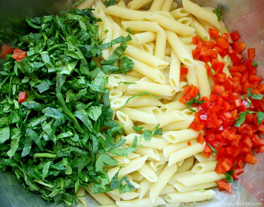 Stainless steel mixing bowl with chopped spinach, cooked penne pasta and diced red peppers