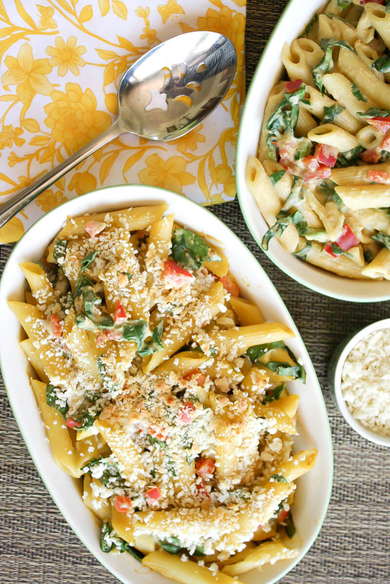 Vertical image of a ceramic dish of baked penne pasta next to a yellow floral cloth napkin with a serving spoon