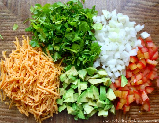 Ingredients needed to make black bean quesadillas chopped and diced on a glass cutting board