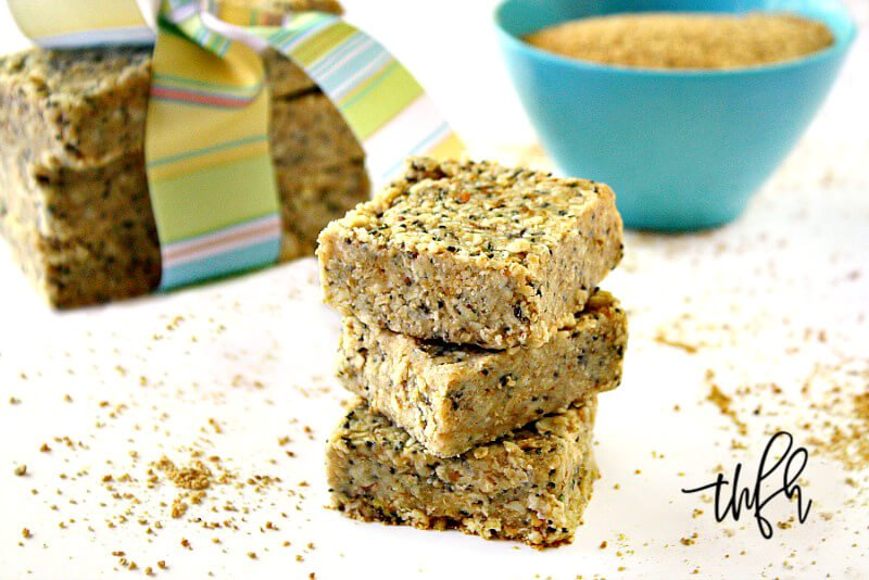 Horizontal image of a stack of three Gluten-Free Vegan No-Bake Hemp and Chia Seed Bars on a white surface with hemp seeds scattered around them