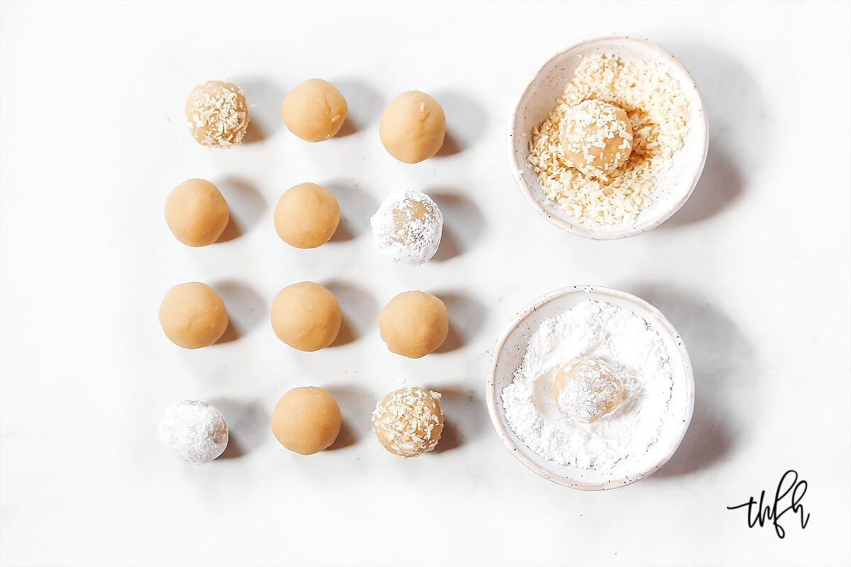 Multiple lemon balls lined up next to two small bowls filled with shredded coconut and powdered sugar