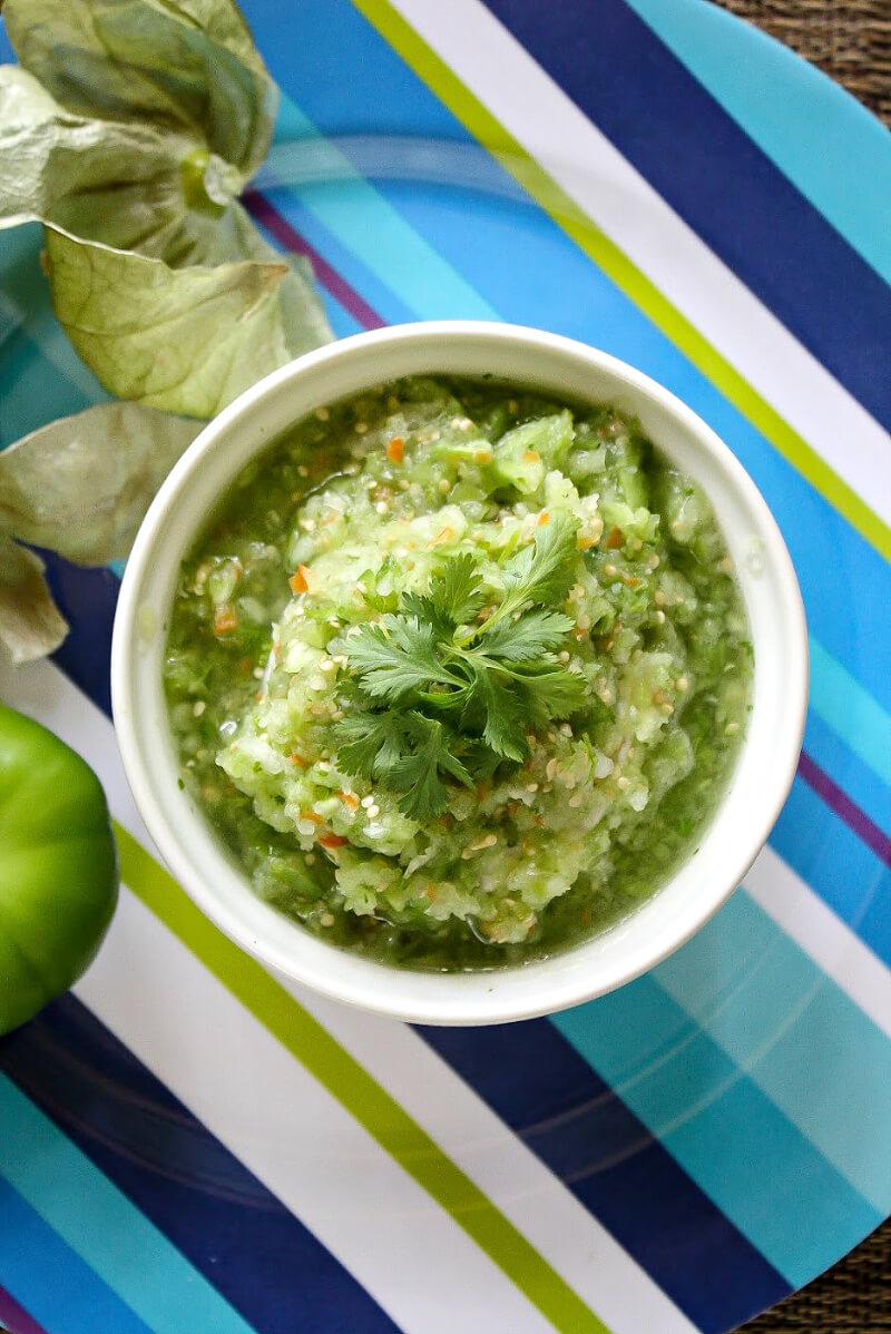 Overhead view of a white bowl of The BEST Homemade Tomatillo Salsa Verde on a blue striped plate