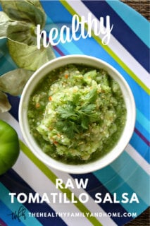 Overhead image of a white bowl of The BEST Homemade Raw Tomatillo Salsa Verde on a blue striped plate with text overlay