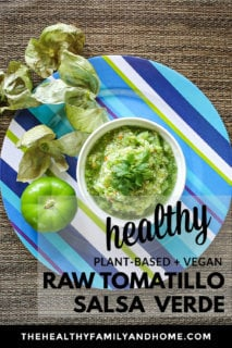 Blue striped plate with a white bowl of The BEST Homemade Raw Tomatillo Salsa Verde on a brown textured background with text overlay