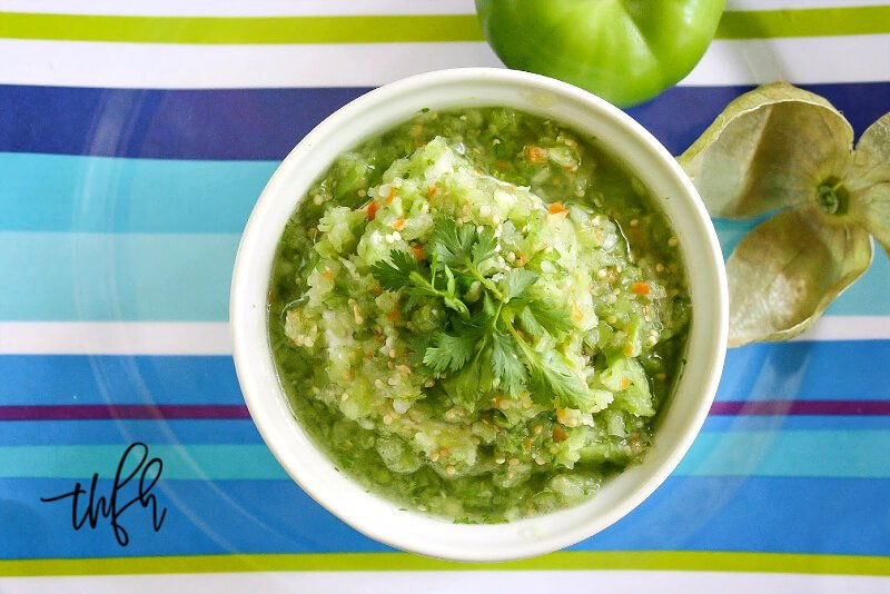 Overhead horizontal image of a white bowl of The BEST Homemade Raw Tomatillo Salsa Verde on a blue striped plate