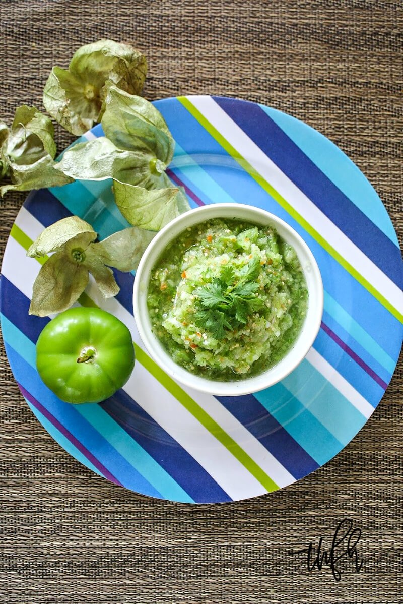 Overhead view of a large blue striped plate with a white bowl of The BEST Raw Homemade Tomatillo Salsa Verde on top of a textured brown surface