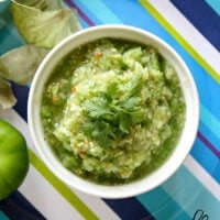 Overhead view of a white bowl filled with The BEST Homemade Raw Tomatillo Salsa Verde on a blue striped plate
