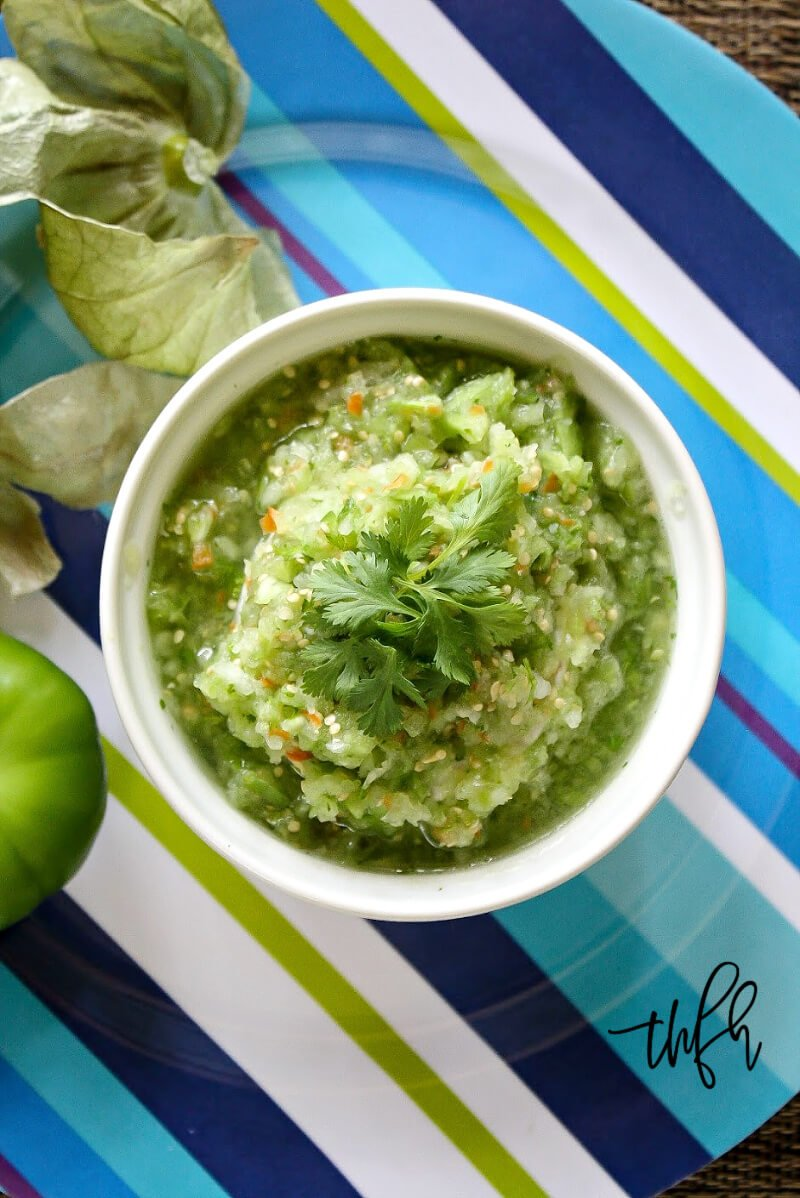 Overhead view of a white bowl filled with The BEST Homemade Raw Tomatillo Salsa on a blue striped plate