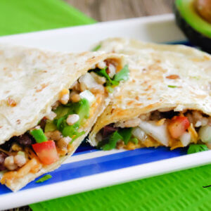 Close up view of two quesadillas on a striped plate on top of a green napkin