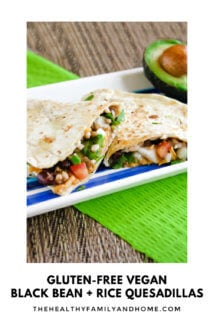 Close up vertical view of two quesadillas on a striped plate on top of a green napkin
