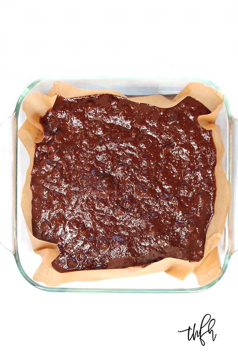 Overhead view of an 8 x 8 glass baking dish of Gluten-Free Vegan Flourless Peanut Butter Swirl Brownies batter on a white surface