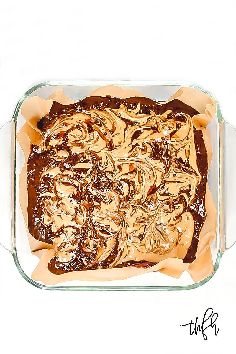 Overhead view of an 8 x 8 glass baking dish with unbaked Gluten-Free Vegan Flourless Peanut Butter Swirl Fudgy Brownie mixture on a white surface