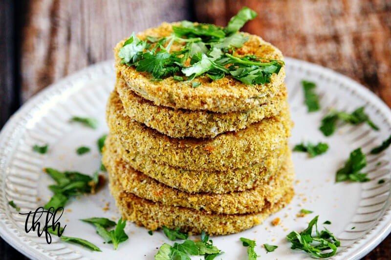 "Horizontal image of a stack of The BEST Gluten-Free Vegan Healthy Oven-Baked ""Fried"" Green Tomatoes on a white plate on a wooden surface"