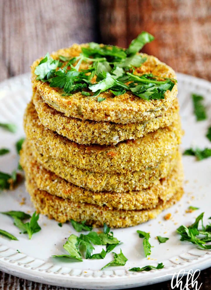 """Vertical image of a stack of The BEST Gluten-Free Vegan Oven-Baked """"Fried"""" Green Tomatoes on a white plate on a wooden surface"""