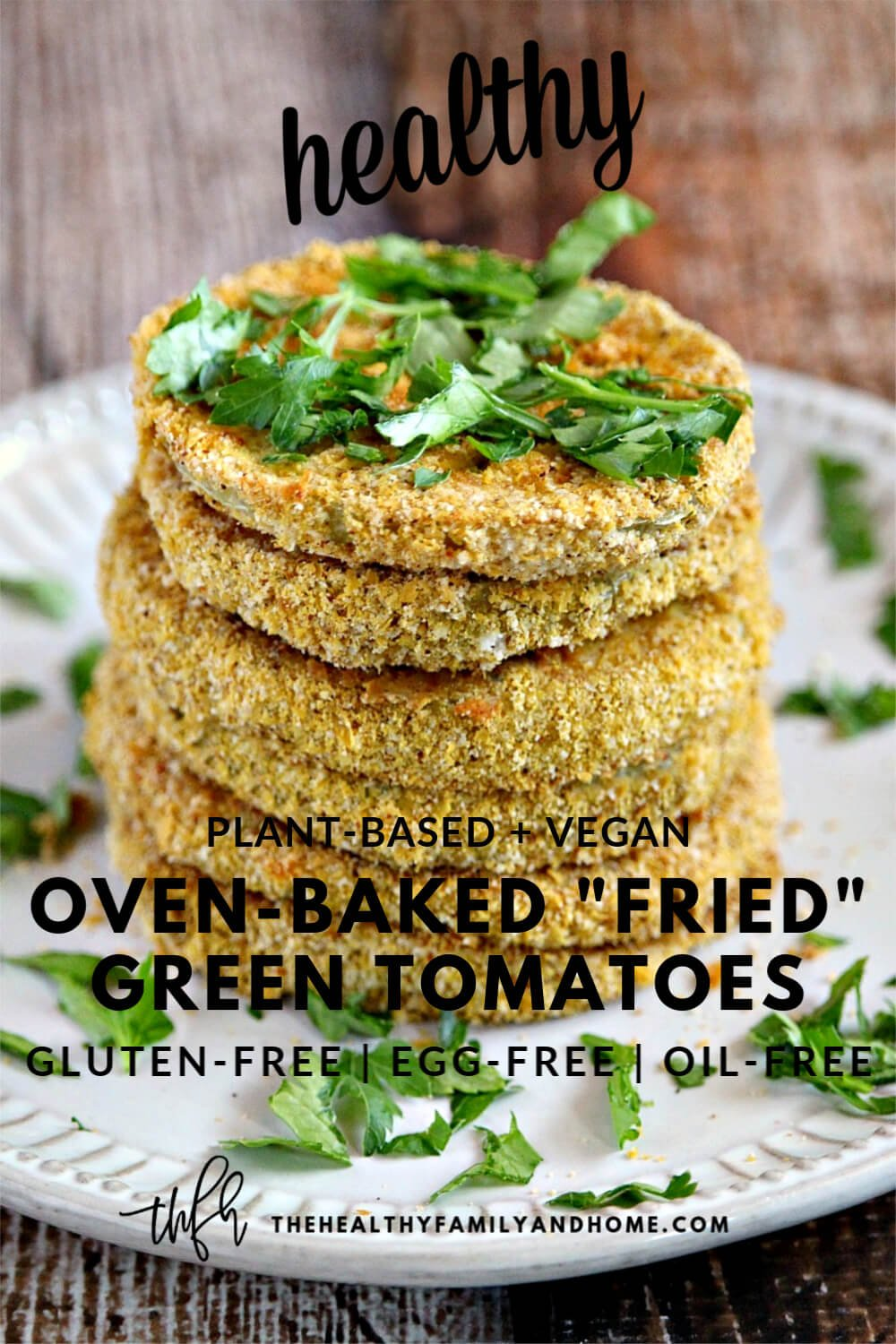 "Vertical image of a stack of The BEST Gluten-Free Vegan Oven-Baked ""Fried"" Green Tomatoes on a white plate on a wooden surface"