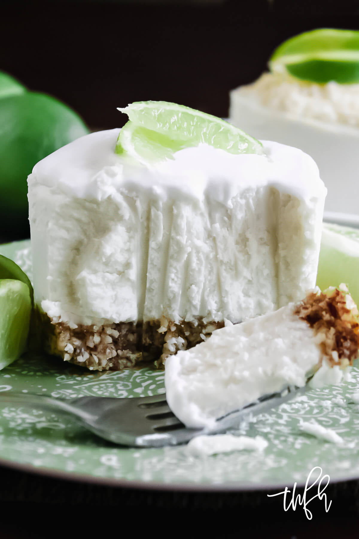 Vertical image of an individual key lime cheesecake with a fork bite taken out on a decorative green plate