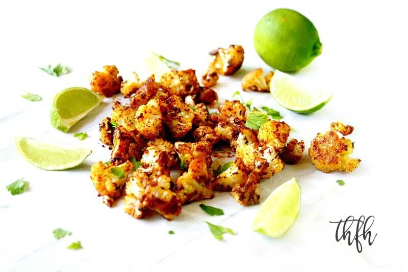 Horizontal image of Gluten-Free Vegan Roasted Cauliflower with Chipotle and Lime scattered over a white marble surface with sliced limes