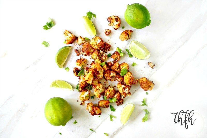 Overhead horizontal view of Gluten-Free Vegan Roasted Cauliflower with Chipotle and Lime scattered over a white marble surface with sliced limes