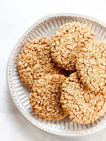 Overhead view of a plate full of Gluten-Free Vegan Flourless Coconut Cashew Cookies on a white background
