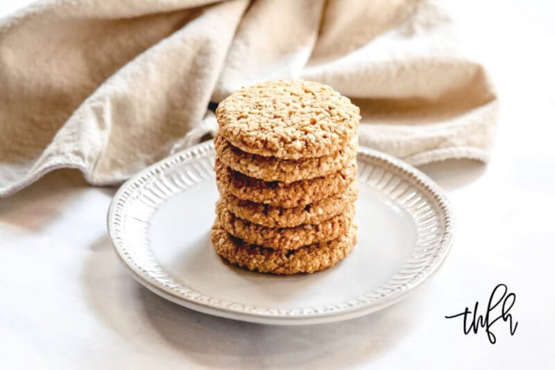 Horizontal image of a stack of Gluten-Free Vegan Flourless Coconut Cashew Cookies on a white plate on a white background