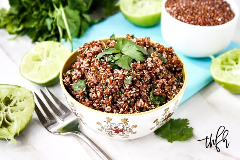 Horizontal image of a small decorative bowl filled with Red Quinoa with Cilantro and Lime next to a fork and squeezed limes to the side
