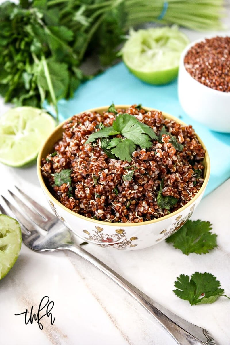 Vertical image of a small decorative bowl filled with Red Quinoa with Cilantro and Lime with a fork next to the bowl and squeezed limes to the side