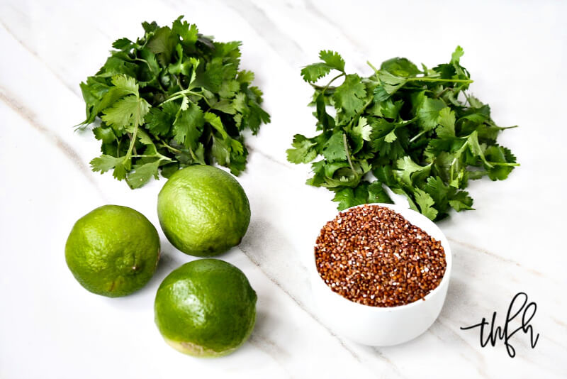 Ingredients needed to make Red Quinoa with Cilantro and Lime spread out on a white marble surface