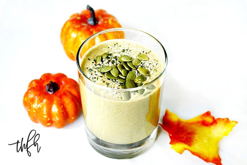 Glass filled with The BEST Vegan Pumpkin Protein Smoothie surrounded by two small pumpkins on a white marble background