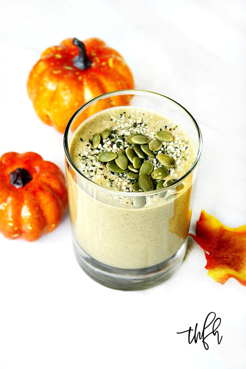Vertical image of a glass filled with The BEST Vegan Pumpkin Protein Smoothie on a solid white marbled surface with two small pumpkins in the background