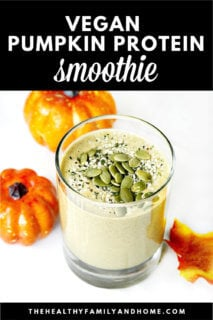 A glass filled with The BEST Vegan Pumpkin Protein Smoothie with pumpkins behind it on a white marble surface and text overlay