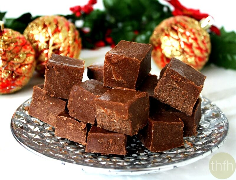 Silver plate with squares of Gluten-Free Vegan No-Cook Healthy Holiday Fudge on a white marble surface with Christmas decorations in the background